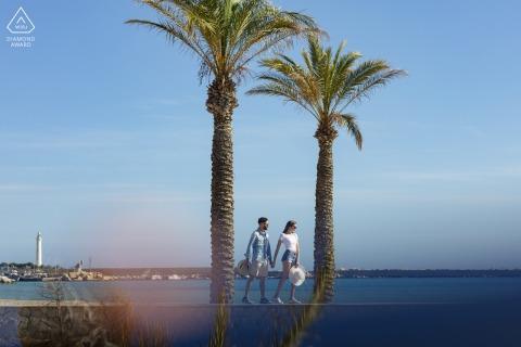 Sesión electrónica de retratos de San Vito Lo Capo Beach para una pareja Paseando por el mar entre dos palmeras