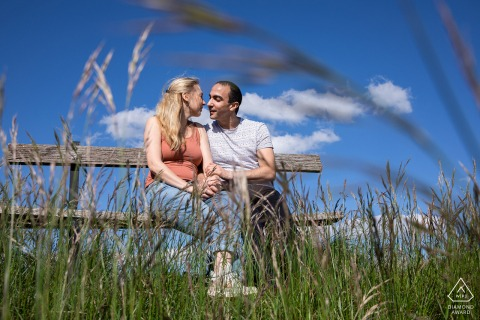 Colline de Sion on-location portrait e-shoot for a couple sitting on a rustic farm bench in the tall rural grass
