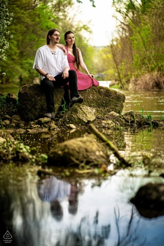 Brno environmental engagement e-session with reflections of the Couple sitting by the river