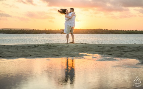 Maceió, Alagoas environmental engagement e-session with a Man and woman smiling and dancing on the beach