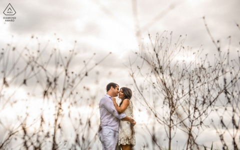 Maceió, Alagoas environmental engagement e-session with the couple hugging on a farm and the dry grass forms a frame for them