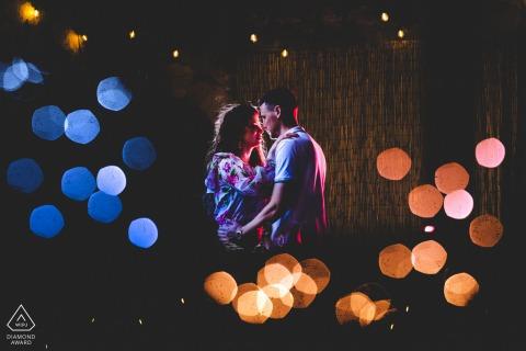 Séance de portraits avant le mariage True Love à Syracuse montrant un couple entouré de lumières colorées bokeh