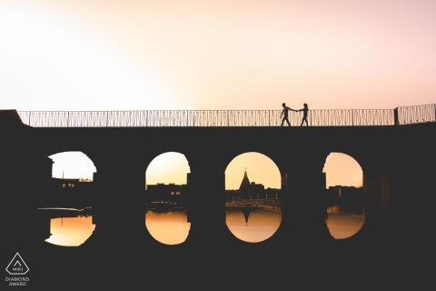True Love Engagement Portrait Session à Syracuse affichant un couple marchant sur le pont pendant le coucher du soleil au printemps en Sicile