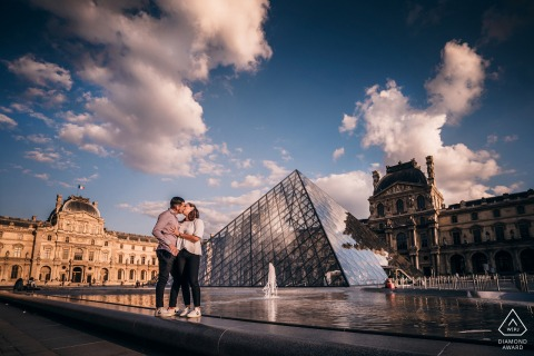 True Love Engagement Portrait Session at the Louvre Museum in Paris showing a couple kissing under the clouds of France
