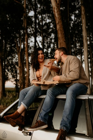 True Love pre wedding Photoshoot in Cascavel of a couple sharing a pizza and love on the roof of a car