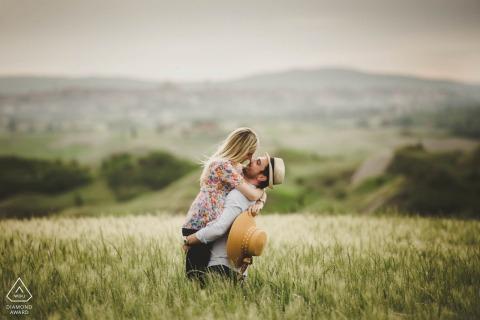 Tuscany countryside True Love Pre-Wedding Portrait Session in Crete Senesi illustrating a couple having fun in the grass fields
