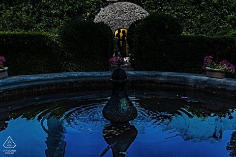 Espagne True Love Engagement Portrait Session aux Patios de Viana à Cordoue montrant un couple au bord d'un bassin d'eau de fontaine