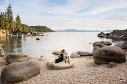 True Love Engagement Posed Portrait à Lake Tahoe, NV capturant un couple s'embrasse assis sur un rocher avec l'étendue de l'eau en arrière-plan