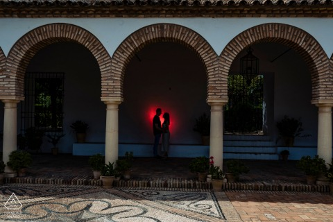 True Love Engagement Posed Portrait at the Patios de Viana in Córdoba capturing a couple under 3 arches with a red backlight spot