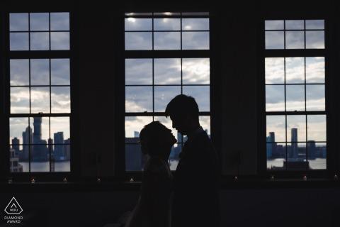 True Love Pre-Wedding Portrait Session à Manhattan illustrant un couple à l'intérieur dans un appartement avec vue sur la ville depuis les fenêtres