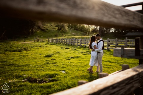 True Love Engagement Picture Session at the Parco Nazionale D'Abruzzo showing a couple near a fence on the grasses of the Abruzzo National Park