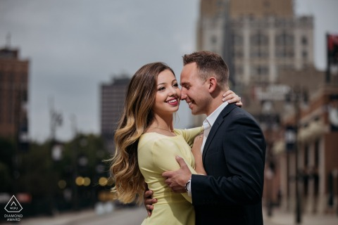 True Love Pre-Wedding Portrait Session in Detroit illustrating a couple with the urban city skyline behind them