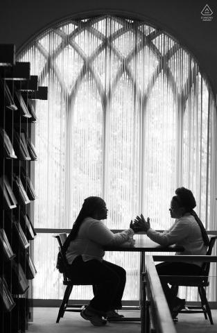 Sesión de retrato de compromiso de amor verdadero en la biblioteca de Emory en Atlanta que muestra a una pareja en la mesa de la biblioteca de teología donde se conocieron