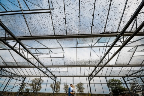 True Love Engagement Portrait Session at the family farm displaying the future bride and groom in the glass roof of the farm