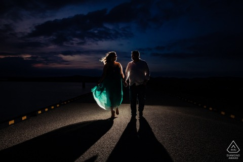 True Love Engagement Portrait Session at Overlook Park in Canyon Lake displaying a couple walking into the light at night