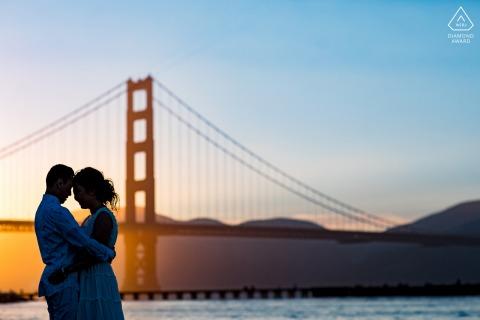 Sesión de retrato previo a la boda de amor verdadero en Crissy Field en San Francisco mostrando una pareja de CA durante Golden Light en el Golden Gate