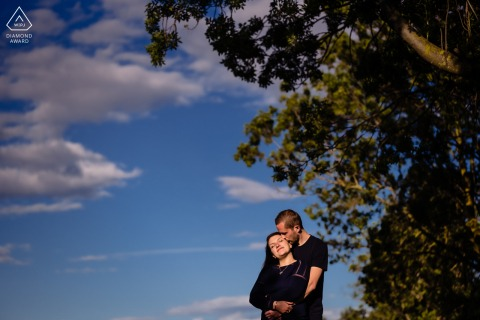 True Love Engagement Picture Session in Montpellier showing a couple embracing near a tree under the sky and clouds