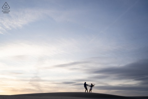 True Love pre wedding Photoshoot in Camargue of a couple playing around on dune at the beach at sunset