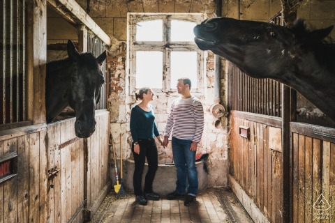 True Love Engagement Portrait Session in Sologne showing a couple inside a horse stable holding hands on the wooden barn floor