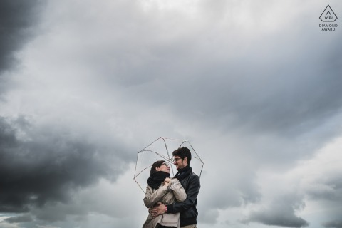 France outdoor True Love Pre-Wedding Portrait Session in Golf du Morbihan capturing a couple under clouds with a single umbrella
