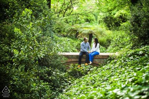 Séance de portrait avant le mariage True Love à Madrid illustrant un couple assis sur un pont dans le parc de la jungle urbaine