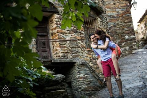 Séance de portrait avant le mariage True Love à Patones montrant un couple jouant dans un village en pierre