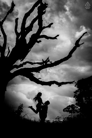 True Love Engagement Portrait Session in at Fazenda Água Limpa in Hidrolândia showing a GO couple silhouetted under a tall tree with strong limbs