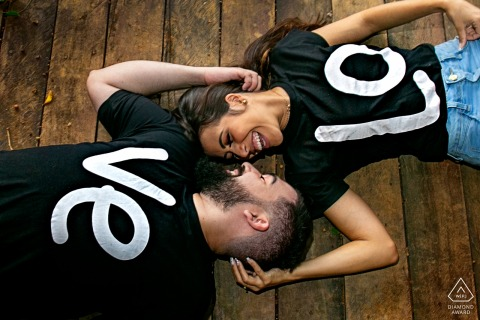 True Love Pre-Wedding Portrait Session at Fazenda Água Limpa in Hidrolândia  illustrating a couple lying on the wooden floor with shirts spelling out L O V E