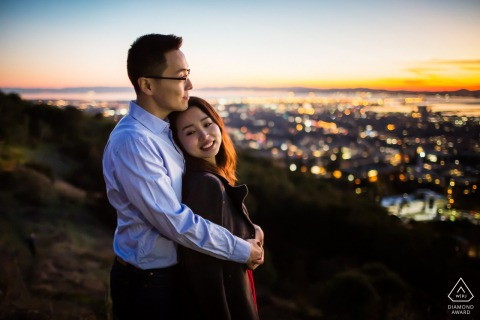 True Love Engagement Portrait Session in UC Berkeley showing a couple Enjoying the spectacular evening view of the city below at sunset