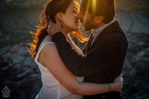 True Love Engagement Portrait Session in Drumheller displaying a couple kissing in the backlit sunshine
