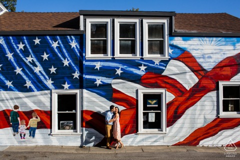 True Love Engagement Posed Portrait in Los Gatos capturing a couple having a kiss before the giant American flag mural