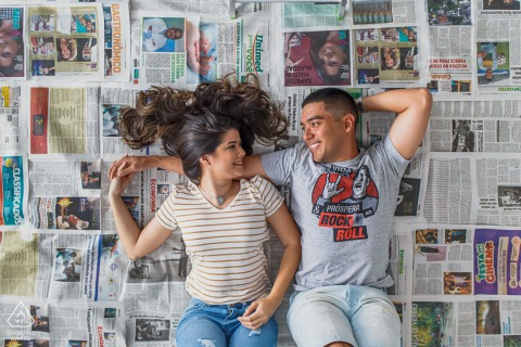 True Love Engagement Portrait Session in Maceió displaying a couple lying down on their backs on a bed of newspapers