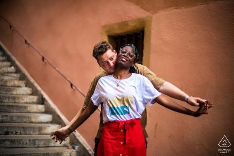 E-session couple Vieux Lyon en France avec enjouement sous les escaliers lors d'une séance d'amour dans le vieux Lyon