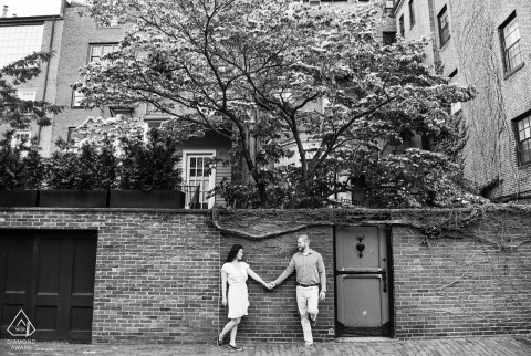 Beacon Hill, Boston couple e-shoot holding hands and looking at each other against brick wall