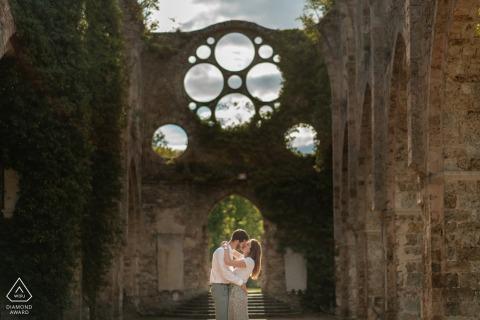 France couple e-shoot à l'Abbaye des Vaux de Cernay avec un baiser encadré dans l'arche du bâtiment