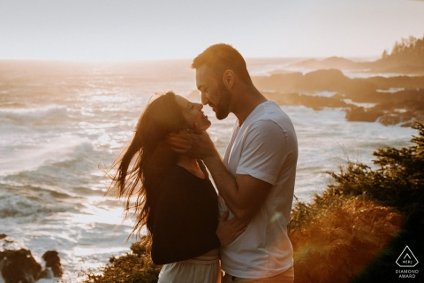 British Columbia couple e-session at Tofino, Vancouver Island kissing with a ocean backdrop with rocks and waves
