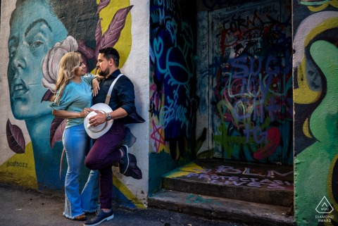 Knoxville couple e-shoot at Market Square standing next to walls covered in beautiful street art
