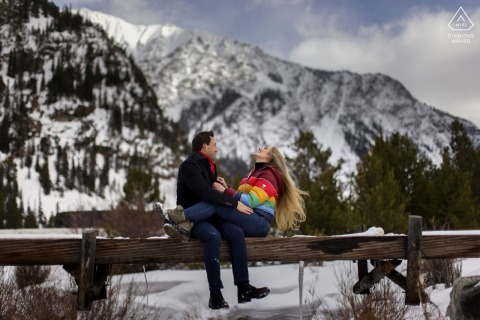 Officers Gulch couple e-session in Colorado share a laugh while sitting on a bridge