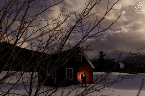 Frisco couple e-session on a tubing hill silhouetted against a red barn in the snow