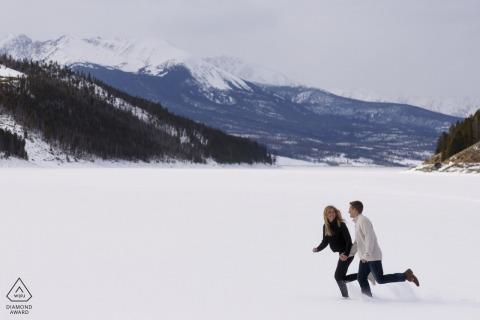 Lake Dillon couple e-shoot run in the snow on the frozen lake