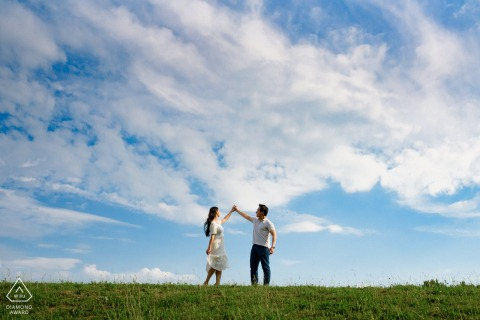 Angrignon Park couple e-session in Montreal, Quebec while standing on hill with cloudy blue sky behind them