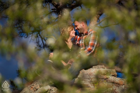 Horsetooth Reservoir, Fort Collins, Colorado couple e-shoot while sitting on rocks surrounded by pine trees