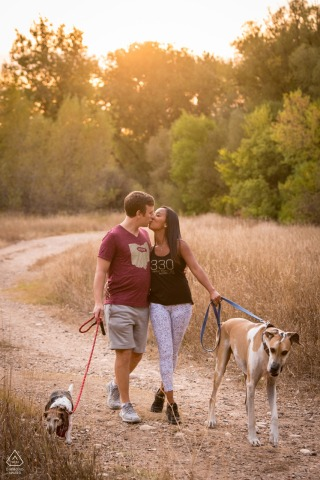 Fort Collins couple e-session Colorado on the rocky dirt trail walking their dogs
