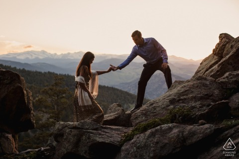 Lost Gultch Overlook couple e-session in Boulder, Colorado with the lovers helping each other up a rocky outcrop for their engagement photos