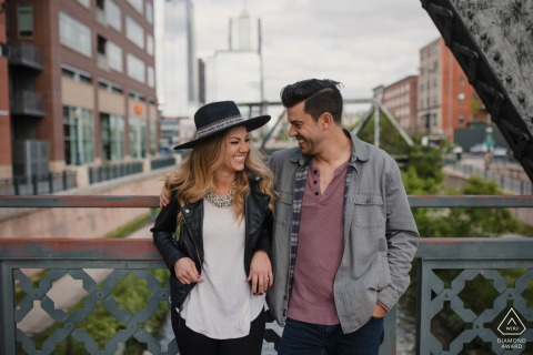 Denver, CO pre wedding e-session for an Engaged couple laughing together on a city bridge