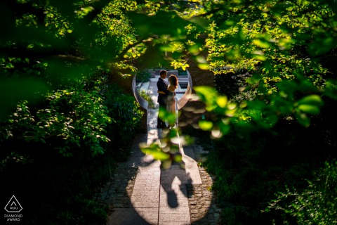 Enid A. Haupt Gardens couple e-session at the Smithsonian Castle, Washington DC standing in the Moongate Arch, framed by spring trees and leaves