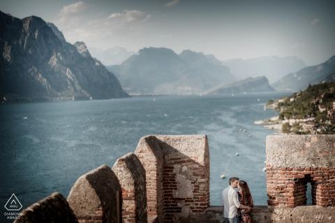 E-session di coppia Castello di Malcesine al Lago di Garda, in alto sopra l'acqua con la coppia che si bacia sulle mura del castello