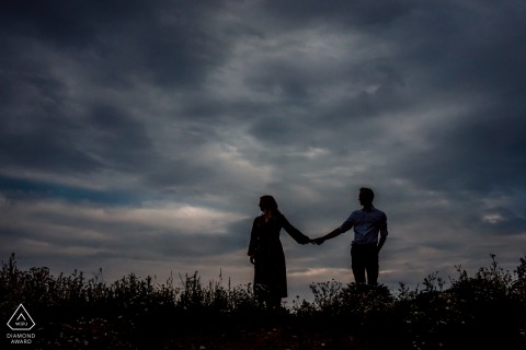 Hengelo coppia e-shoot durante il tramonto con nuvole scure e mano che tiene