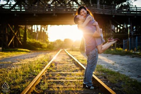 Santa Cruz couple e-shoot on the railroad tracks with some sunset Jumping for joy