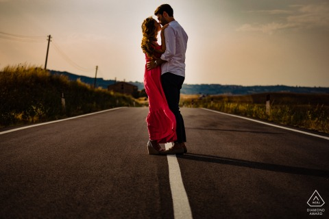 Val D'orcia couple session in Tuscany in the middle of the road with warm light